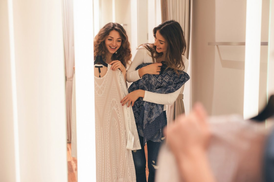 Two friends trying on clothes in a dressing room.